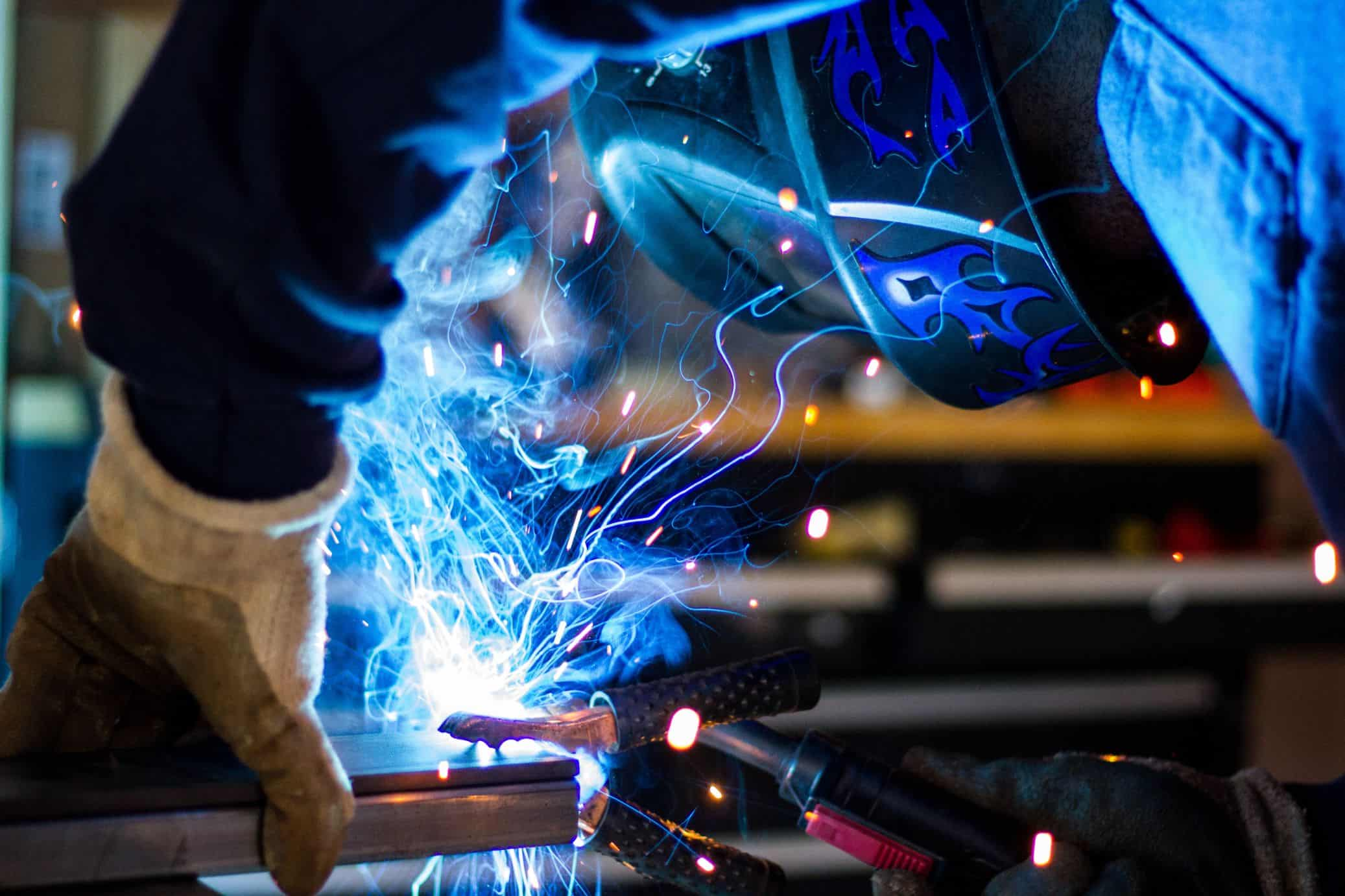 man holding welding tool and blue sparks