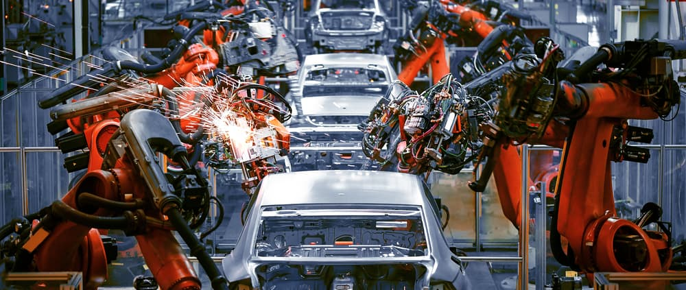 Line of automated welding robots in automotive plant dealing with semiconductor automotive shortage